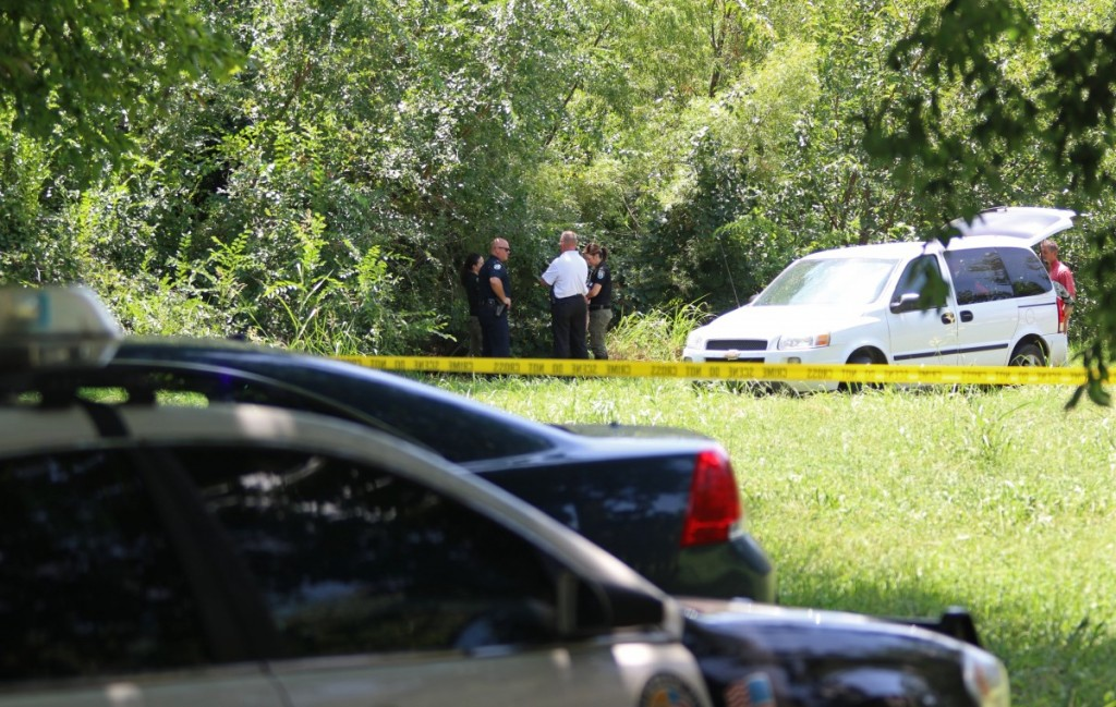 Midwest City police and state medical examiner's office personnel investigate a body that was found in a creek bed this morning near Harr Drive and Adair Boulevard. (Staff photo by Jeff Harrison)