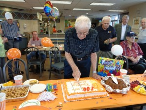 Dr. Gerald Hefley cuts a piece of his 100th birthday cake at a celebration at Midwest City Whattaburger on Tuesday.