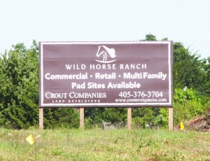 A sign sits on the land where a new commercial development will take place at the northeast corner of SW 59th and Mustang Road.