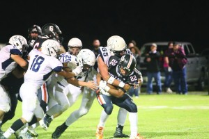 Minco's defense swarms a Wayne ball carrier in a game between the two teams on Friday.