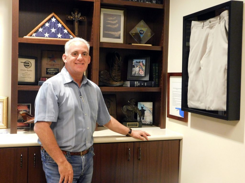 Sen. Paul Rosino (R-Oklahoma City) stands in his office near three displays very important to his past and mission as an Oklahoma legislator, he says – a poem written by his sister to commemorate his November 2017 swearing in and shoes and pants worn by him every day he campaigned for the District 45 senate seat. (Staff photo by Traci Chapman)