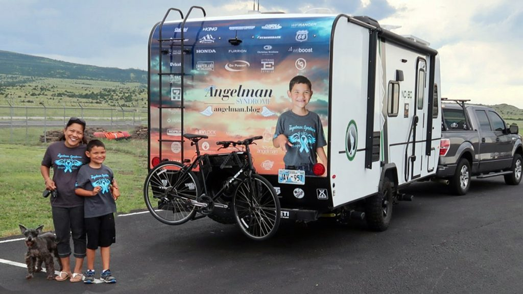 """Maggie and Matthew outside their camper July 14, as they got underway on their """"camper campaign,"""" designed to spread awareness about Angelman Syndrome.  (Provided photo)"""