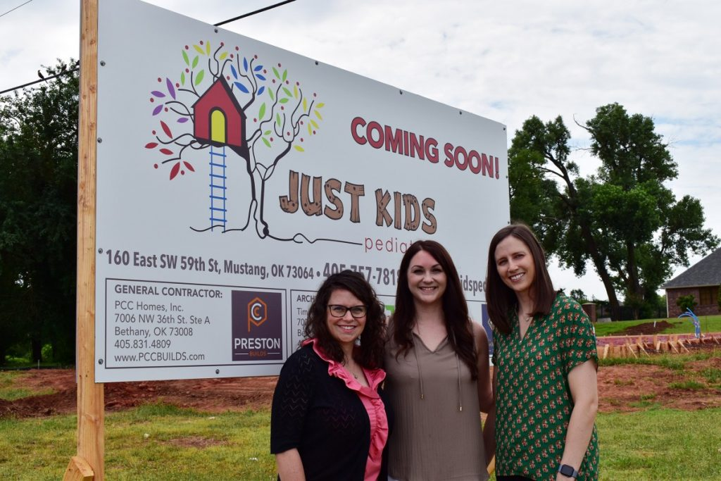 Sarah Palm, MD; Katie Wertzberger, APRN; and Taylor Iago, PA-C stand before the site of the Just Kids Pediatrics location currently under construction just east of the intersection of SW 59th Street and Mustang Road. The clinic is currently set for an early 2020 opening. (Staff photo by Traci Chapman)