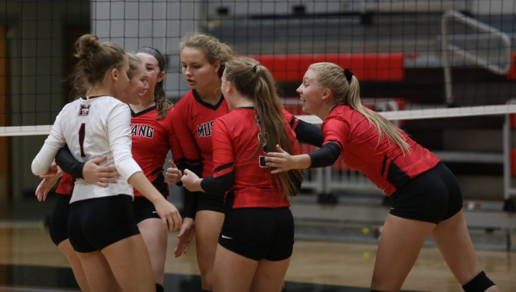 Mustang volleyball players chat during a match earlier this season. (Staff photo by Jeff Harrison)