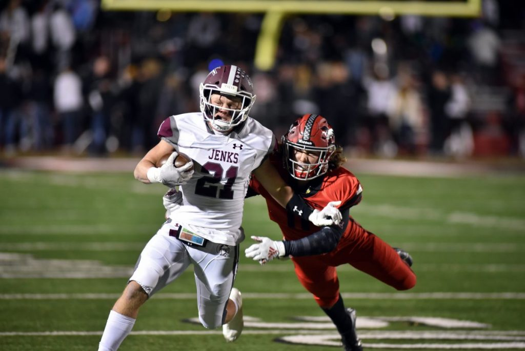 Mustang senior Liam Krivanek (11) tries to wrap up Jenks running back Will Cox (21) Friday night during a Class 6A-I state playoff football game at Bronco Stadium. Jenks used a big third quarter to roll to  55-28 win in the first round. (Photo by Alan Chapman)