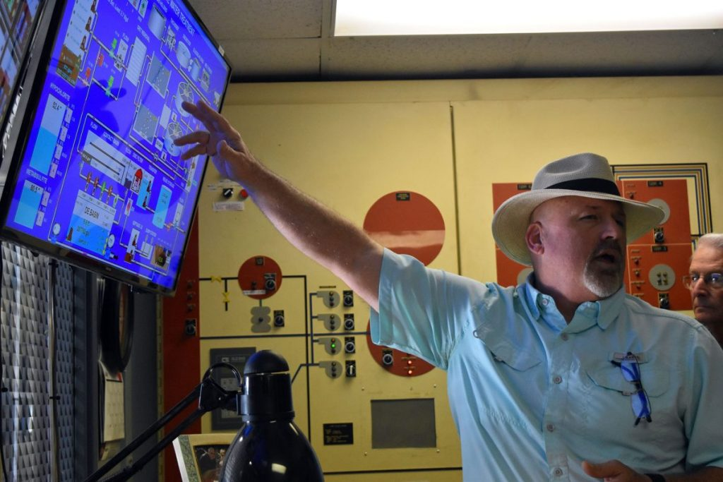 Mustang Water Reclamation Facility lead operator Kevin Cahoon explains how functions are monitored at the plant during a tour conducted as part of a September reopening celebration. (File photo)