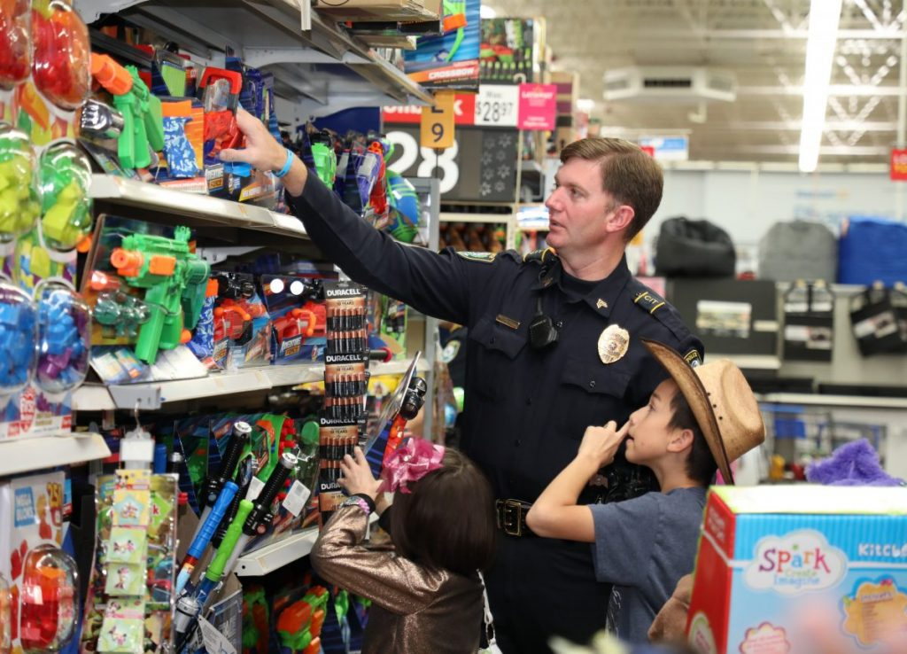 Midwest City Police Officer Rollie Branham helps children pick out toys Sunday during Shop with a Cop at Walmart. (Photo by Jeff Harrison)
