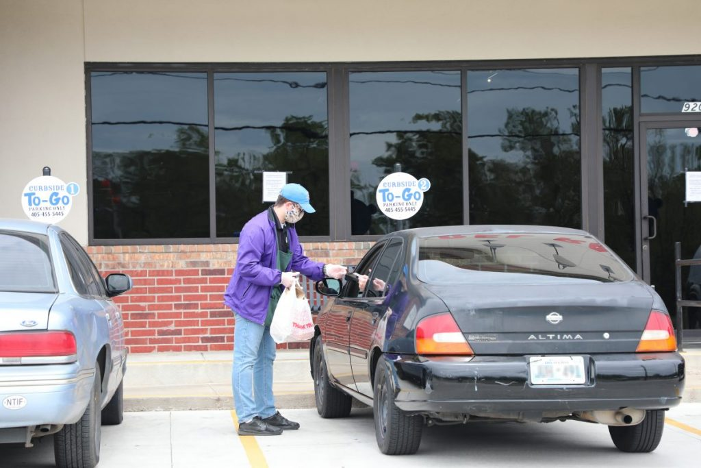 An employee at Del Rancho takes a customer order at the curbside pickup. (Staff photo by Jeff Harrison)