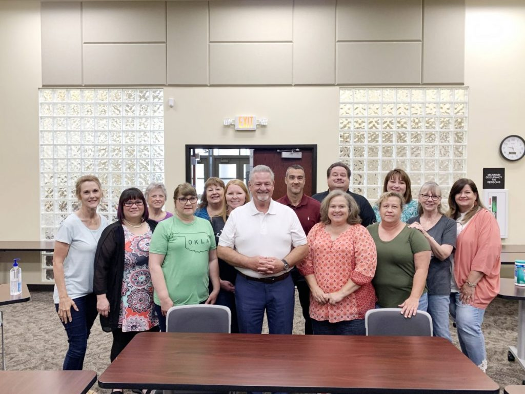Dr. Jim McCharen, center, celebrates with district staff and supporters at the 2020 Cooperative Council for Oklahoma School Administration awards banquet.