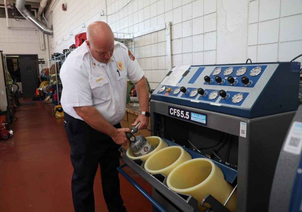 Fire Chief Bert Norton uses a new compressor to refill an air bottle at Station No. 1. (Photo by Jeff Harrison)