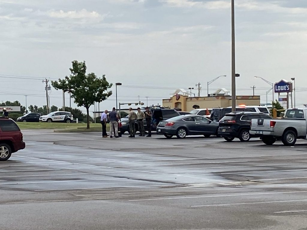 Investigators surround a suspicious item found in a car parked in the Mustang Lowe's parking lot. The item was confirmed to be a bomb, officials say. (Photo/Jeff Harrison)