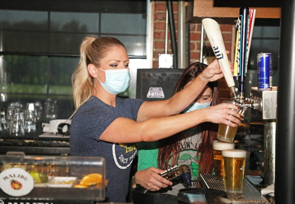 An employee at Henry Hudson's wears a mask while pouring drinks. Midwest City issued an ordinance requiring all restaurant and bar staff to wear a mask to prevent the spread of COVID-19. (Photo by Jeff Harrison)