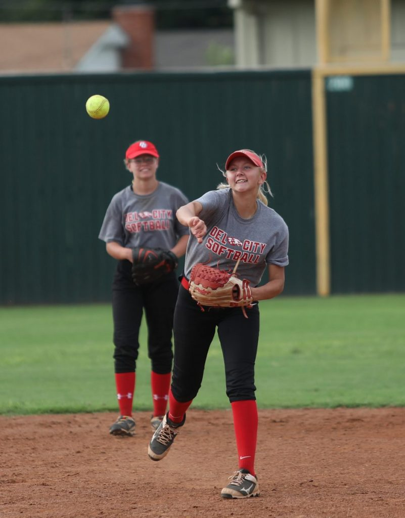 Del City's Taylor Mesna throws to first base during practice last week. (Photo by Jeff Harrison)