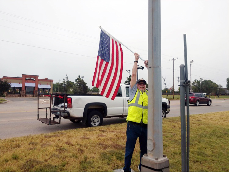 Mustang American Legion Post 353 member George Hurley works Saturday as part of the team putting up the Avenue of Flags. The patriotic symbols will remain on display along state Highway 152 and Mustang Road through Sept. 20. (Photo by Traci Chapman)
