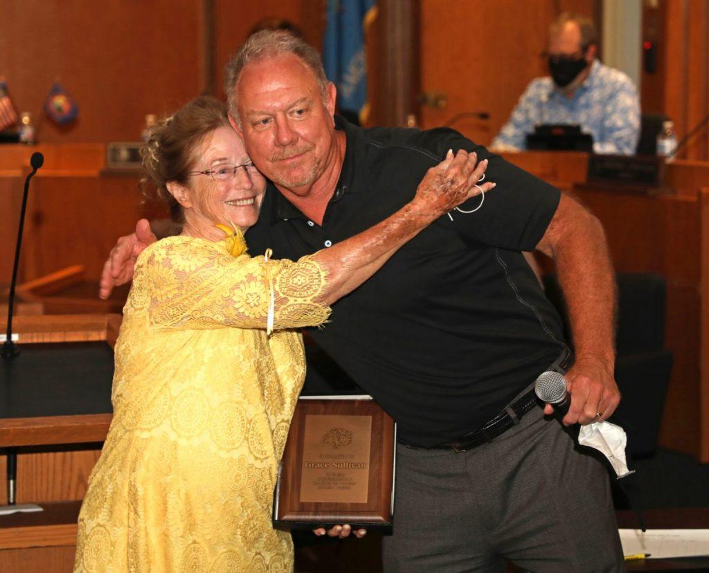Grace Sullivan hugs Vaughn Sullivan, assistant city manager, during a Sept. 8 city council meeting. (Photo by Jeff Harrison)