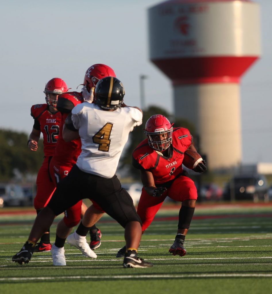 Javion Hunt runs behind a block last Friday against Midwest City. (Photo by Jeff Harrison)