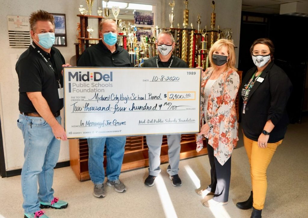 The Mid-Del Public Schools Foundation presents a $2,600 check to the Midwest City High School band program from the Joe Groves memorial fund. Pictured, from left, Mark Hensley, Jon Davis, superintendent Rick Cobb, Mid-Del Public Schools Foundation board president Pam Dimski and Lindse Barks, Foundation director. (Photo by Stacey Boyer)