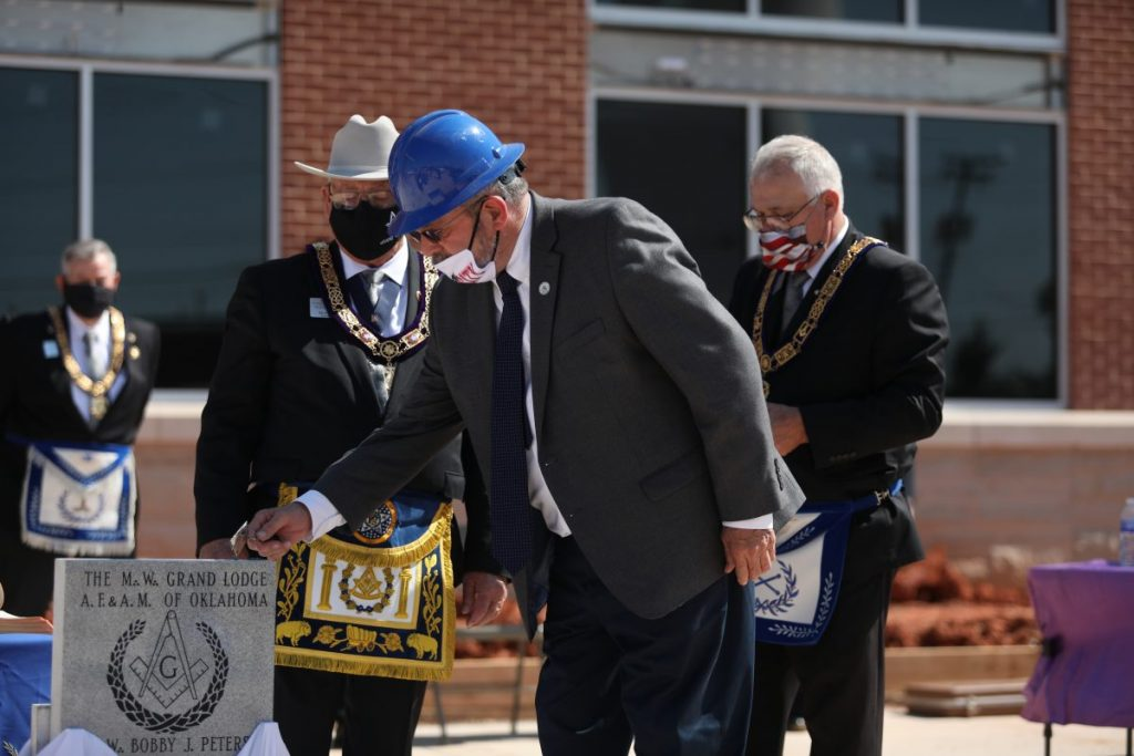 Del City Mayor Floyd Eason spreads cement on the cornerstone to symbolically set the stone during a ceremony at the new Del City Library on Oct. 5. (Photo by Jeff Harrison)