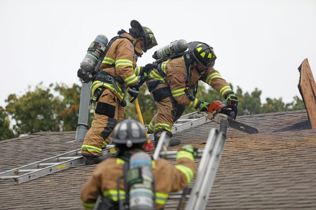 Midwest City firefighters practice ventilating a roof during a training exercise last Friday morning. The department conducted full training exercise at a home that is slated for demolition. (Photo by Jeff Harrison)