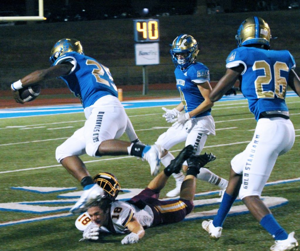 Choctaw High School's RJ Jackson rolls over the Putnam North defense as Jax Burchett (4) and CJ Smith (26) look to lend a hand. Jackson returned Friday after sitting out with injury since week five. (PHOTO BY RYAN HORTON)