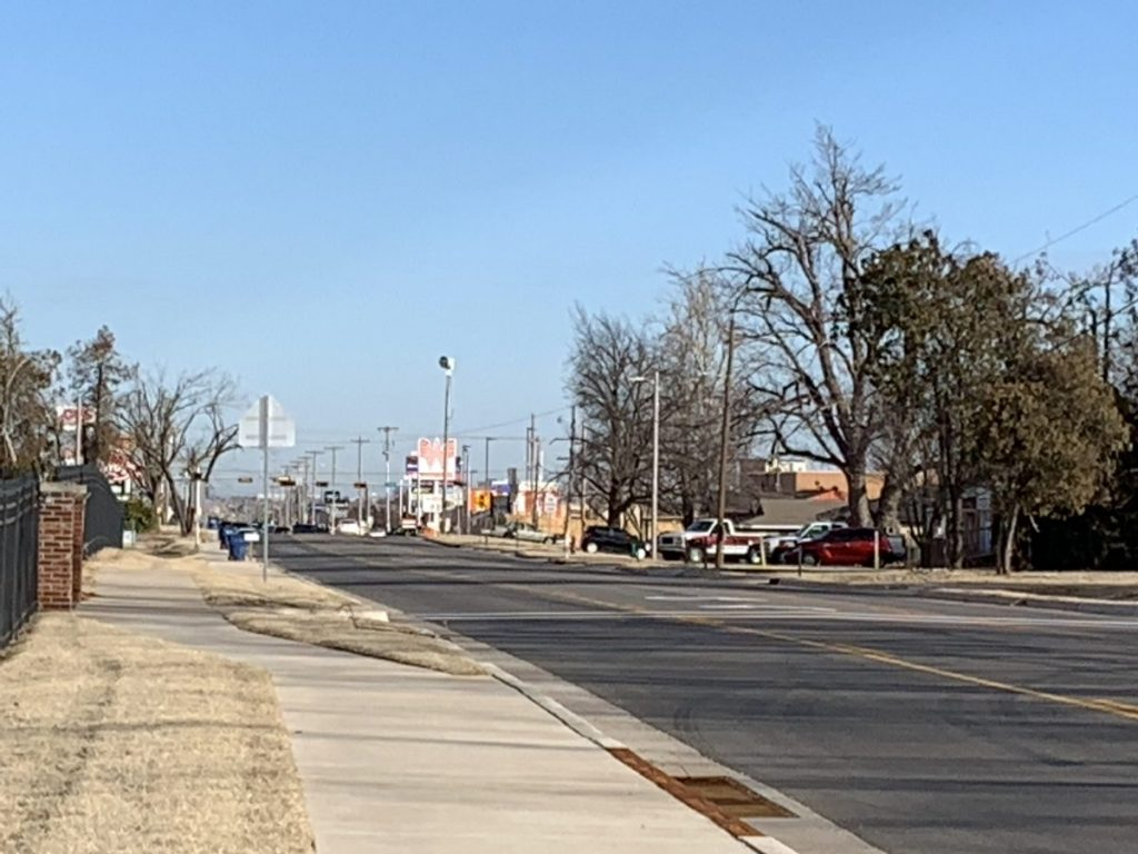 Traffic moves along widened and redeveloped South Mustang Road Tuesday. The project is complete, except for storm water system work expected to move forward in February. That will not impact drives or the roadway itself, City Manager Tim Rooney says. (Photo by Traci Chapman)
