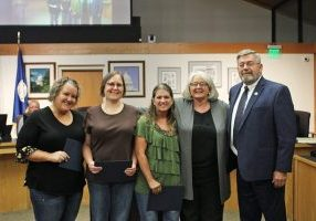 Kristi Tasker, Cyndi Harwell, and Stacie Freitas were recognized by Mayor Floyd Eason and Councilwoman Pam Finch for their efforts cleaning up flower beds and welcome signs in Del City. (Photo by Anthony Thomas)